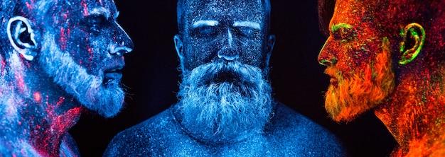 Porträt von drei bärtigen männern, gemalt in fluoreszierenden pulvern. Premium Fotos