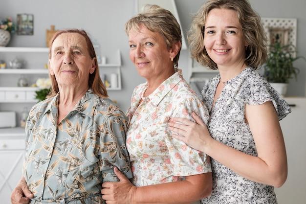 Porträt von drei generationsfrauen, welche die kamera zusammen steht betrachten Kostenlose Fotos