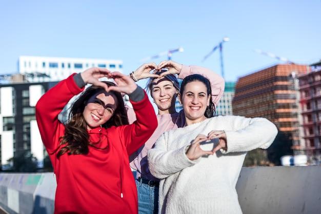 Porträt von drei jungen frau, die fingergestenherz beim lächeln zeigt Premium Fotos