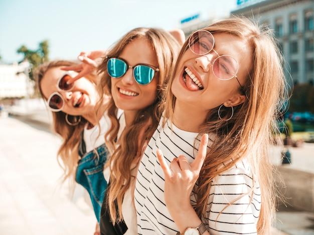 Porträt von drei jungen schönen lächelnden hippie-mädchen in der modischen sommerkleidung. sexy sorglose frauen, die auf der straße aufwerfen positive modelle, die spaß in der sonnenbrille haben umarmen Kostenlose Fotos