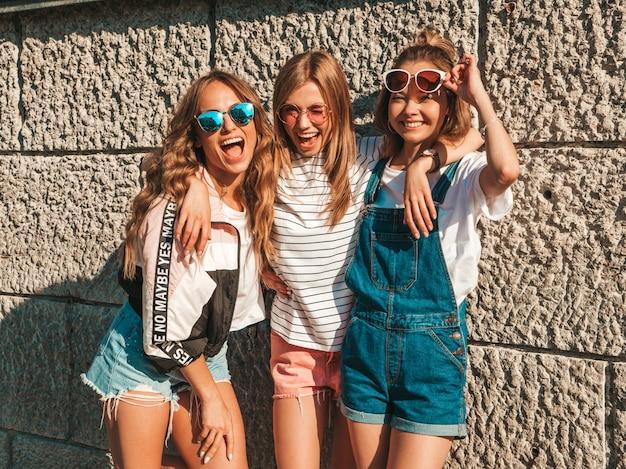 Porträt von drei jungen schönen lächelnden hippie-mädchen in der modischen sommerkleidung. sexy sorglose frauen, die in der straße nahe wand aufwerfen positive modelle, die spaß in der sonnenbrille haben umarmen Kostenlose Fotos