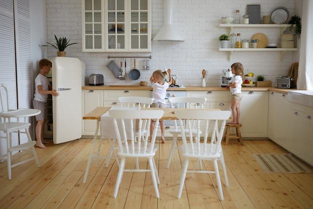 Porträt von drei unabhängigen kindergeschwistern, die das abendessen selbst vorbereiten, während die eltern bei der arbeit sind. kinder machen gemeinsam frühstück in der küche. konzept für essen, küche, küche, kindheit und ernährung Kostenlose Fotos