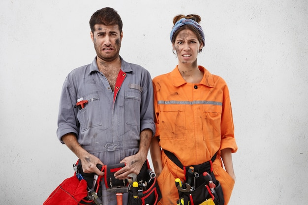 Porträt von elenden erschöpften servicemitarbeitern, die den ganzen tag etwas reparieren, schmutzige gesichter haben Kostenlose Fotos