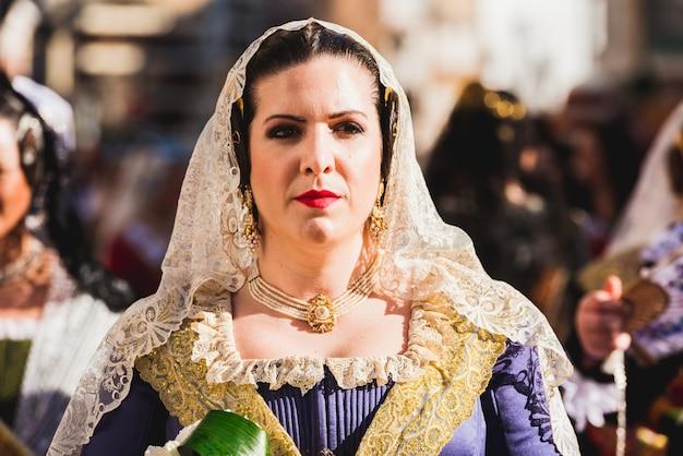 Porträt von falleras-frauen, die das traditionelle kostüm von fallas am tag des angebots an die jungfrau während der parade tragen Premium Fotos