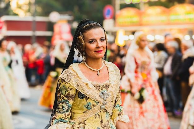Porträt von falleras-frauen, die das traditionelle kostüm von fallas tragen, das der jungfrau während der parade durch die straßen von valencia anbietet Premium Fotos