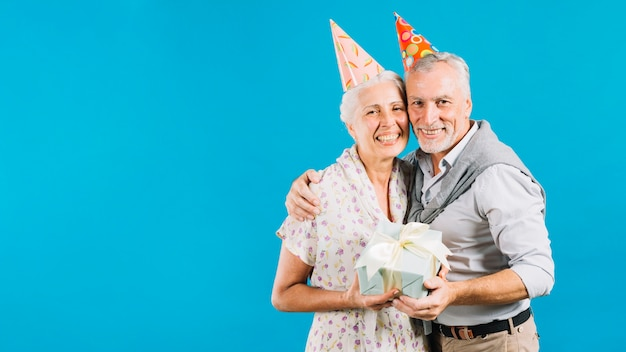 Porträt von glücklichen älteren paaren mit geburtstagsgeschenk auf blauem hintergrund Kostenlose Fotos