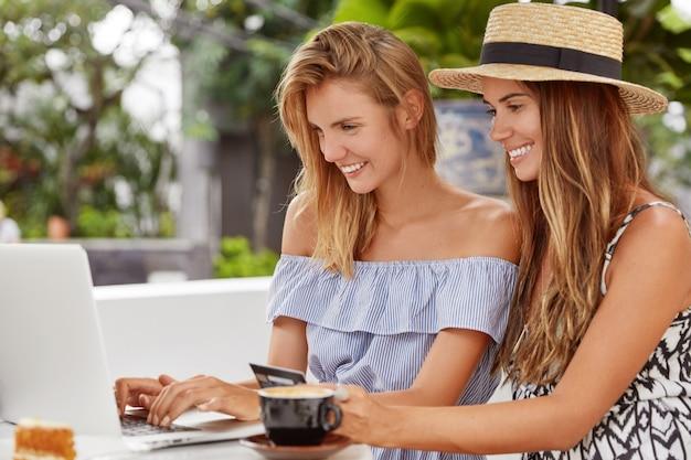 Porträt von glücklichen jungen europäischen frauen, die online einkaufen, die nummer der kreditkarte auf dem laptop eingeben, für den online-kauf bezahlen, gemeinsam im café nachbauen, heißes aromatisches getränk trinken Kostenlose Fotos