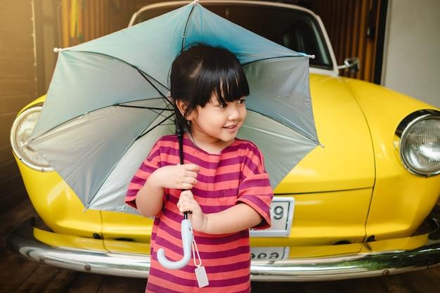 Porträt von glücklichen kindern mit einem regenschirm. regen oder sonnenlicht im sommer schützen Premium Fotos