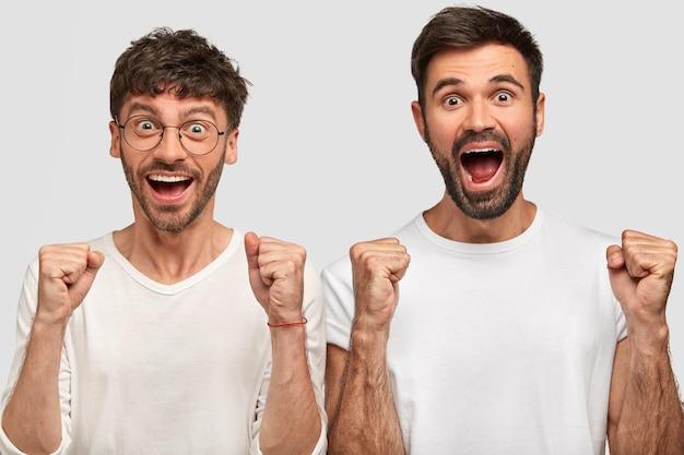 Porträt von glücklichen überglücklichen bärtigen männern, die fäuste ballen und freudig ausrufen, positivität ausdrücken, erfolg freuen, in weißen lässigen t-shirts gekleidet, nebeneinander stehen. erfolgskonzept Kostenlose Fotos