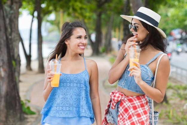 Porträt von hübscher frau zwei, die frischen saft während weg in den park-touristen der jungen mädchen trinkt Premium Fotos