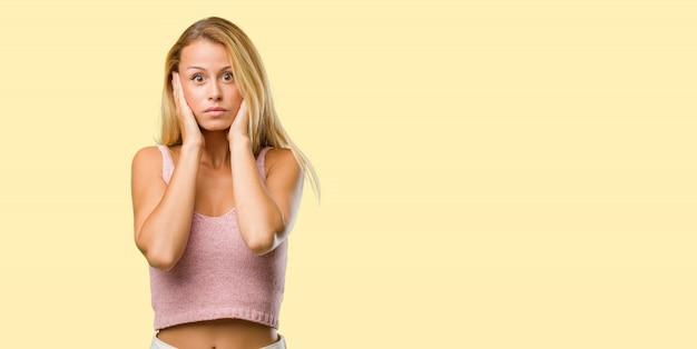 Porträt von jungen hübschen blondinebedeckungsohren mit den händen Premium Fotos