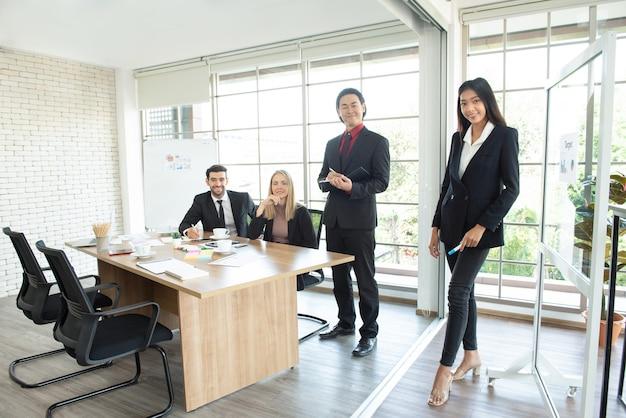 Porträt von jungen und erfolgreichen kaukasischen und asiatischen mitarbeitern im anzug tragen treffen und betrachten kamera, während im arbeitsraum stehen Premium Fotos