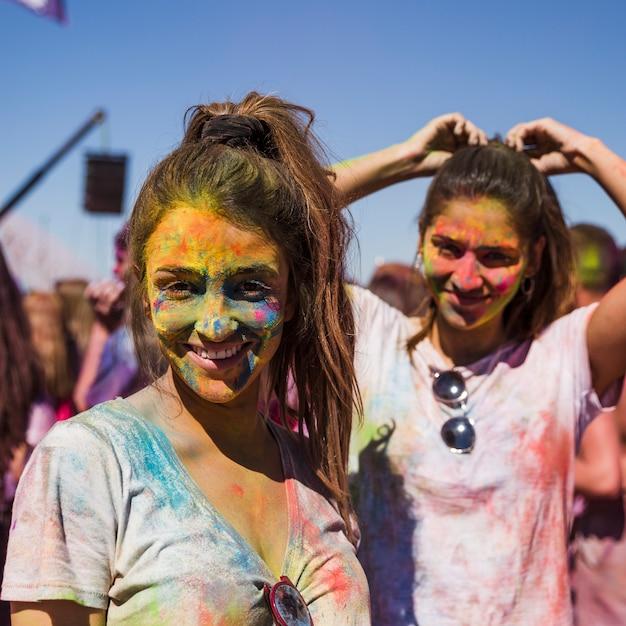 Porträt von lächelnde junge frauen mit holi farben auf ihrem gesicht, das kamera betrachtet Kostenlose Fotos