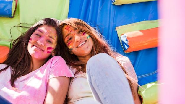 Porträt von lächelnde junge frauen mit holi farbfarbe auf ihrem gesicht, das kamera betrachtet Kostenlose Fotos