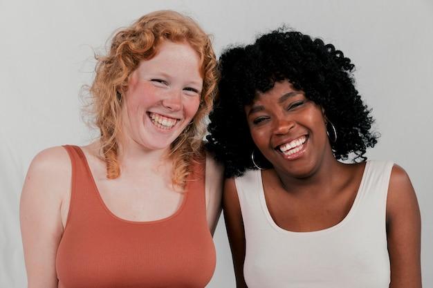 Porträt von lächelnden afrikanischen und blonden jungen frauen gegen grauen hintergrund Kostenlose Fotos