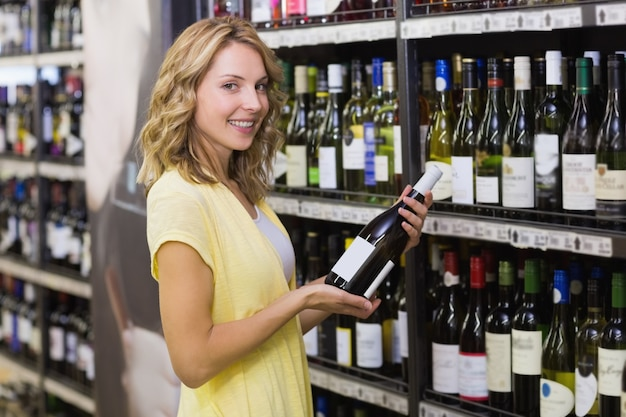 Porträt von lächelnden hübschen blondinen, die eine weinflasche in ihren händen haben Premium Fotos