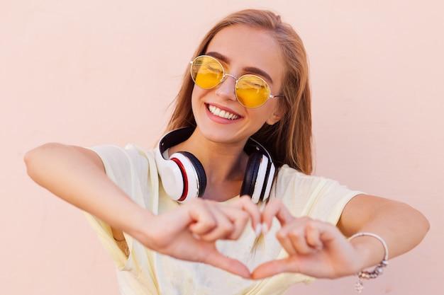 Porträt von lächelnden jungen frauen der schönheitsmode mit gelber sonnenbrille, kopfhörer Premium Fotos