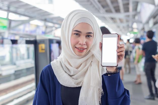 Porträt von moslemischen frauen kleidete im hijab, leere anzeige der show von smartphone an. Premium Fotos