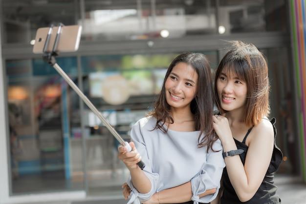 Porträt von netten zwei lächelnden freundinnen, die ein selfie am einkaufszentrum machen. Premium Fotos