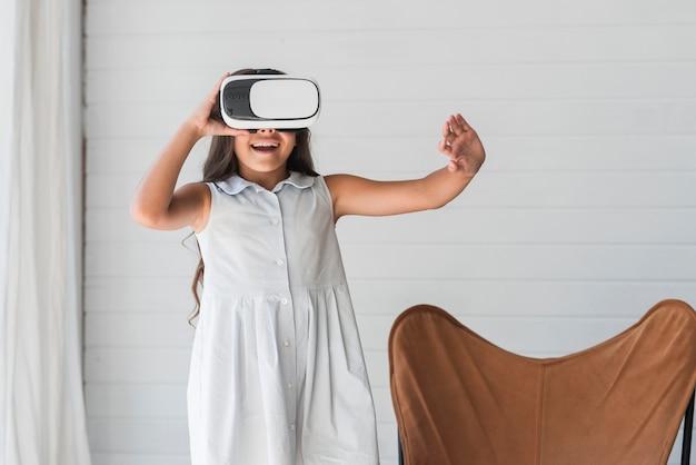 Porträt von tragenden schutzbrillen der virtuellen realität des mädchens, die ihre hand in einer luft berühren Kostenlose Fotos