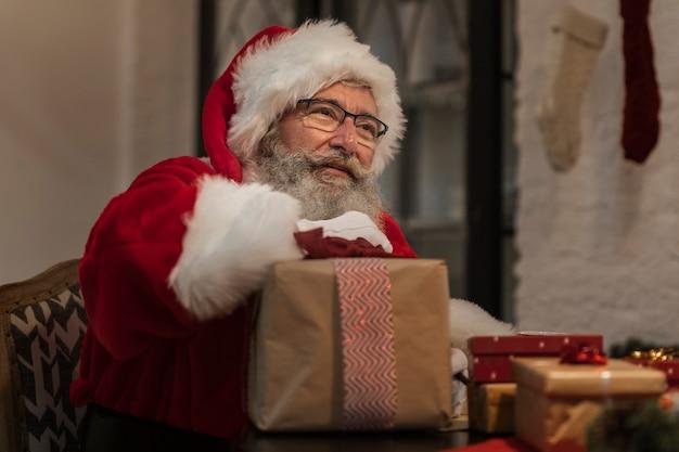 Porträt von weihnachtsmann ein geschenk halten Kostenlose Fotos