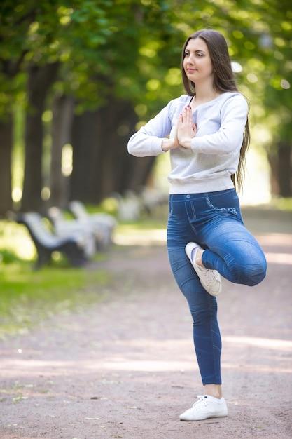 Porträt von yogi frau stehend in vrikshasana pose Kostenlose Fotos