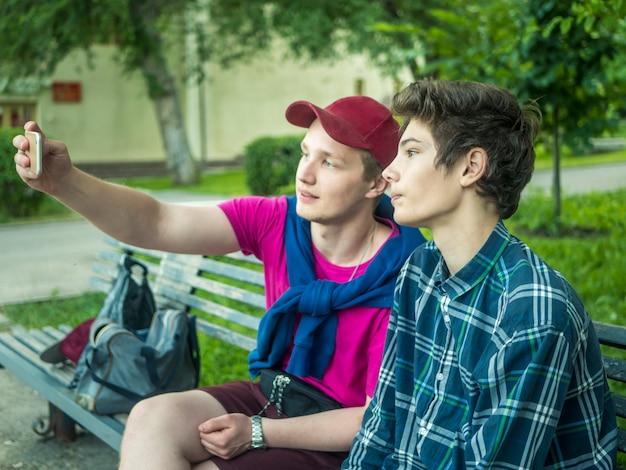 Porträt von zwei attraktiven jungen brüdern, die draußen ein selbstporträt unter verwendung eines telefons machen Premium Fotos