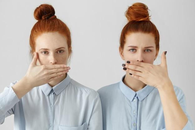 Porträt von zwei attraktiven rothaarigen frauen in identischen hemden, die lippen mit händen bedecken Kostenlose Fotos