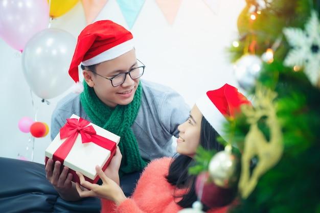 Porträt von zwei behaarten romantischen paaren des brunet geben seiner dame weihnachtsweihnachtsgeschenk des neuen jahres sitzen auf liegesofacouch im dekorativen haus zuhause Premium Fotos