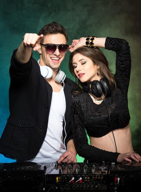 Porträt von zwei djs mit mixer im club. Premium Fotos
