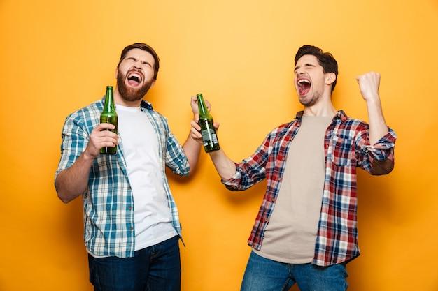 Porträt von zwei fröhlichen jungen männern, die bierflaschen halten Premium Fotos