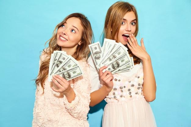 Porträt von zwei glücklichen begeisterten blonden frauen, die freuenden gewinn der sommerkleidung tragen und bargeld lokalisiert über blauer wand halten Kostenlose Fotos