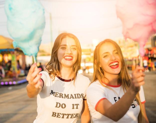 Porträt von zwei glücklichen freundinnen, die süßigkeitsglasschlacke halten Kostenlose Fotos