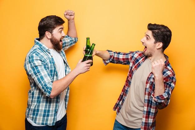 Porträt von zwei glücklichen jungen männern, die mit bier rösten Premium Fotos