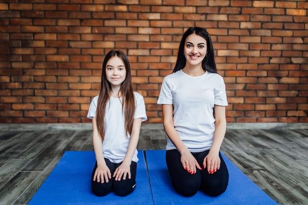 Porträt von zwei jungen flexiblen mädchen, die auf