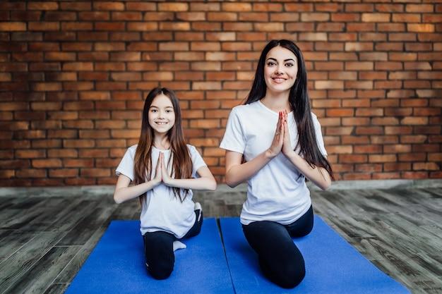 Porträt von zwei jungen flexiblen mädchen, die auf yogamatte sitzen und vor der ausbildung sich vorbereiten. in der yogamitte. Premium Fotos