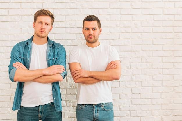 Porträt von zwei jungen männlichen freunden mit ihren armen kreuzte stellung gegen weiße wand Kostenlose Fotos