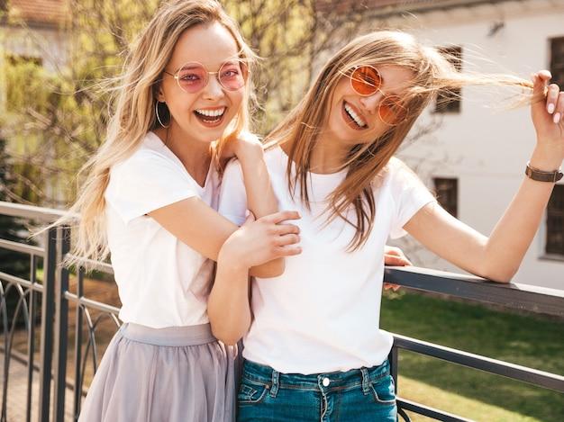 Porträt von zwei jungen schönen blonden lächelnden hippie-mädchen im weißen t-shirt des modischen sommers kleidet. . positive modelle, die spaß in der sonnenbrille haben Kostenlose Fotos