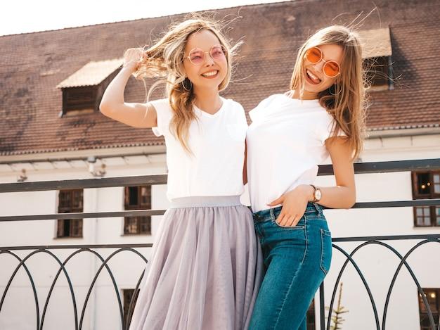 Porträt von zwei jungen schönen blonden lächelnden hippie-mädchen im weißen t-shirt des modischen sommers kleidet. . positive models, die spaß haben Kostenlose Fotos