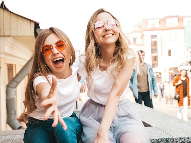 Porträt von zwei jungen schönen blonden lächelnden hippie-mädchen im weißen t-shirt des modischen sommers kleidet. sexy sorglose frauen, die auf straße sitzen. positive modelle, die spaß in der sonnenbrille haben Kostenlose Fotos