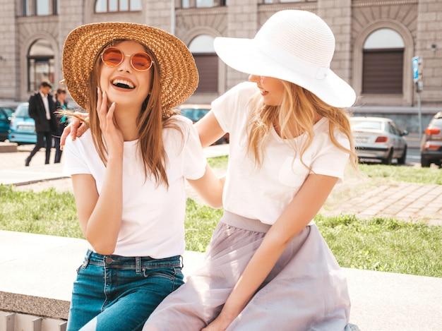 Porträt von zwei jungen schönen blonden lächelnden hippie-mädchen im weißen t-shirt des modischen sommers kleidet. Kostenlose Fotos