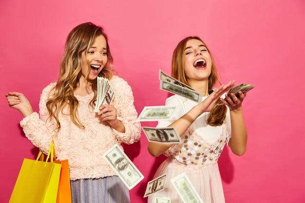 Porträt von zwei jungen stilvollen lächelnden blonden frauen, die einkaufstaschen halten. frauen gekleidet in sommer hipster kleidung. positive modelle, die geld über rosa wand ausgeben Kostenlose Fotos