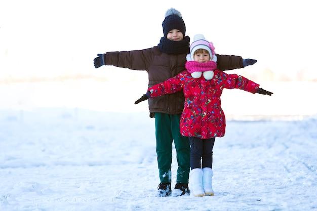Porträt von zwei kindern, die draußen im verschneiten wintertag spielen Premium Fotos