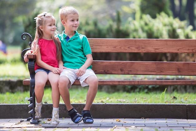 Porträt von zwei recht netten kindern junge und mädchen, die spaßzeit auf einer bank im sommerpark draußen haben. Premium Fotos