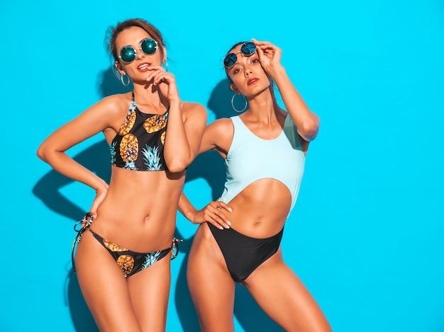 Porträt von zwei schönen sexy lächelnden frauen in badeanzügen der sommerbadebekleidung. trendy heiße models, die spaß haben. mädchen in der sonnenbrille lokalisiert auf blau Kostenlose Fotos
