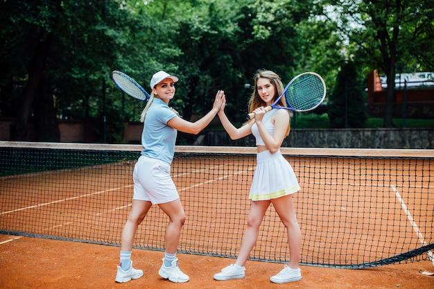 Porträt von zwei sportlichen mädchen auf gericht, tennisspieler mit schlägern beendete wettbewerb. Premium Fotos