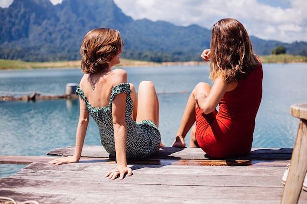 Porträt von zwei touristischen freundinnen in sommerkleidern auf urlaubsreise um thailand khao sok see mit schönem bergblick. Kostenlose Fotos