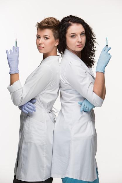 Porträt von zwei weiblichen chirurgen, die spritzen zeigen Kostenlose Fotos