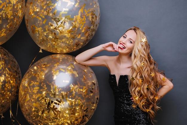 Porträt wunderschöne verspielte junge frau mit langen lockigen blonden haaren, die spaß mit großen luftballons voll mit goldenen lametta auf schwarzraum haben Kostenlose Fotos