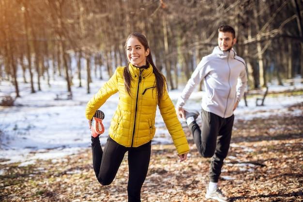 Porträtansicht des jungen glücklichen attraktiven schönen lächelnden fitness-sportpaares in der wintersportkleidung, die im verschneiten wald erwärmt. Premium Fotos